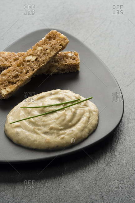 Garnished Hummus and bread slices on plate