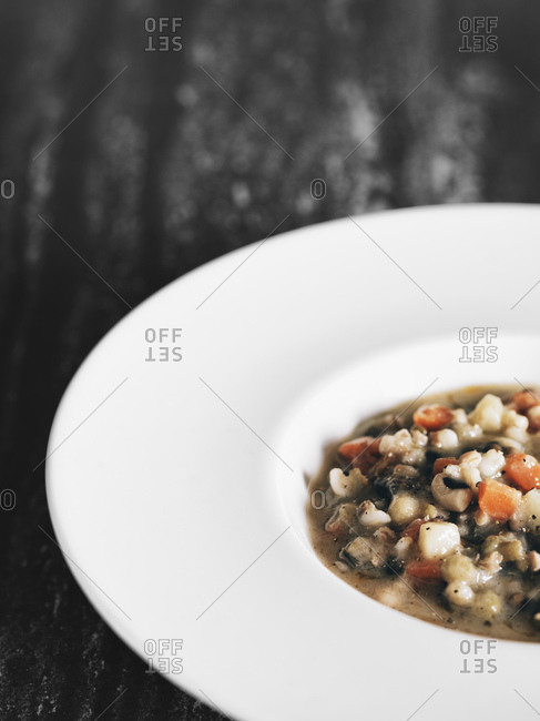 White dish with vegetable soup- partial view