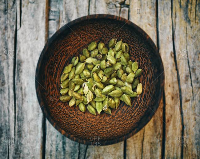 Cardamom capsules in wooden bowl