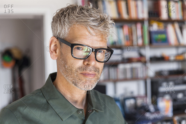 Portrait of mature man with grey hair and stubble wearing glasses at home
