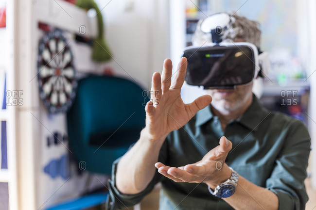 Portrait of mature man at home using Virtual Reality Glasses