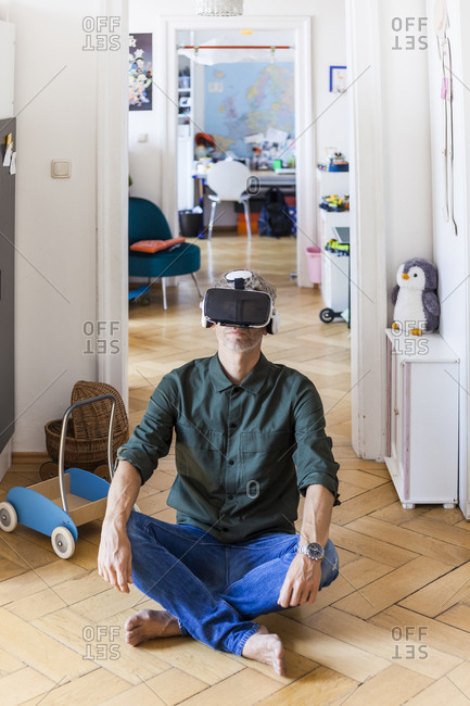 Mature man sitting on the floor at home using Virtual Reality Glasses