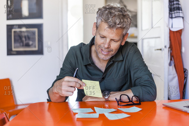 Portrait of content mature man sitting at table at home looking at notepad