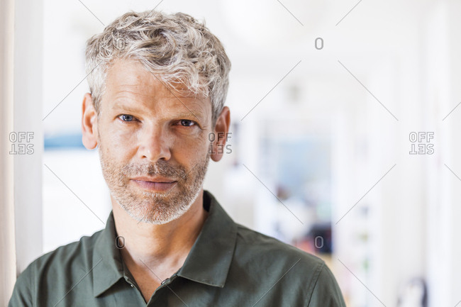 Portrait of mature man with grey hair and stubble at home