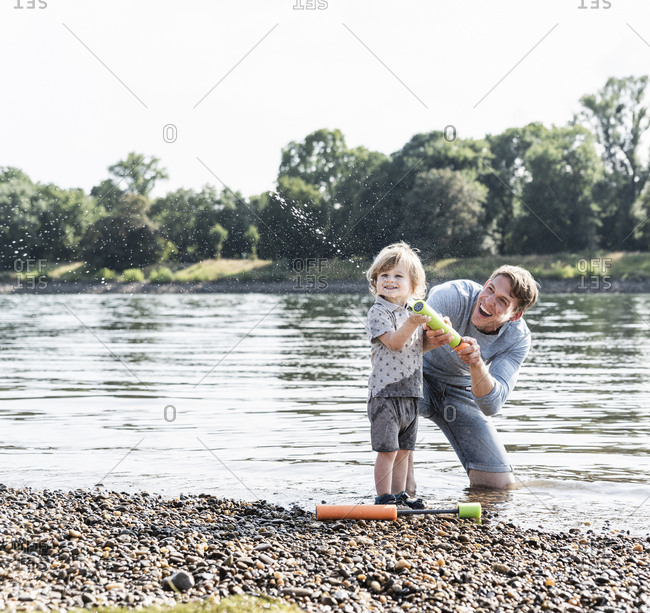 Father and son having fun at the riverside- playing with a water gun
