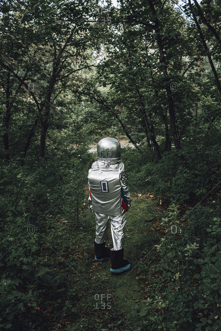 Spaceman exploring nature- walking in forest