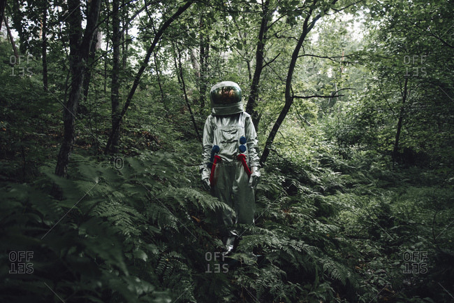 Spaceman exploring nature- looking at forest