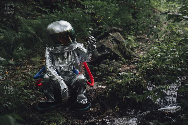 Spaceman exploring nature- crouching at a brook in forest