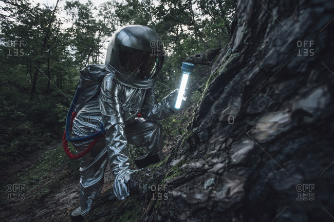 Spaceman exploring nature- using a torch