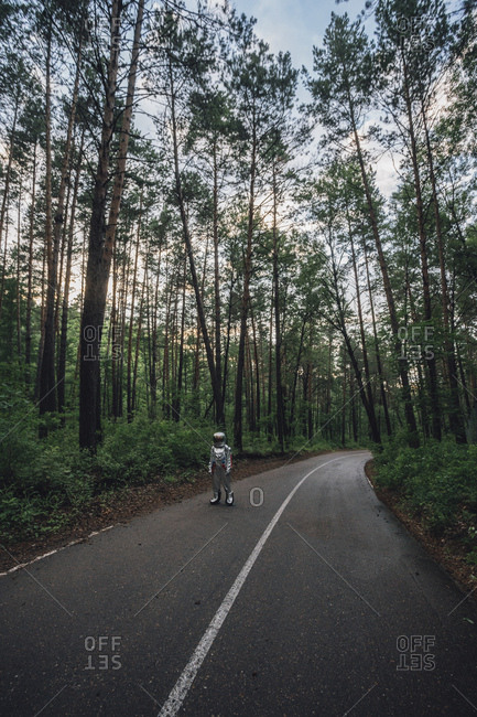 Spaceman exploring nature- standing on road in forest