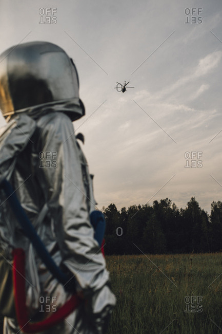Spaceman exploring nature- watching helicopter