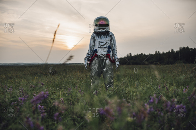 Spaceman exploring nature- standing in meadow-