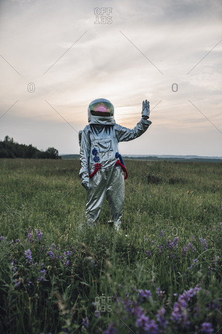 Spaceman exploring nature- standing in meadow- waving