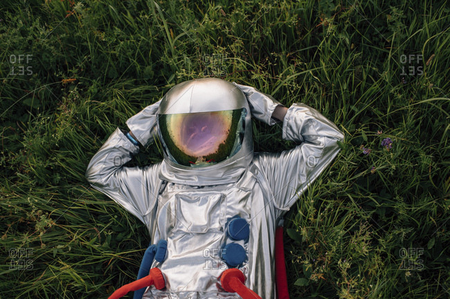Spaceman exploring nature- relaxing in meadow