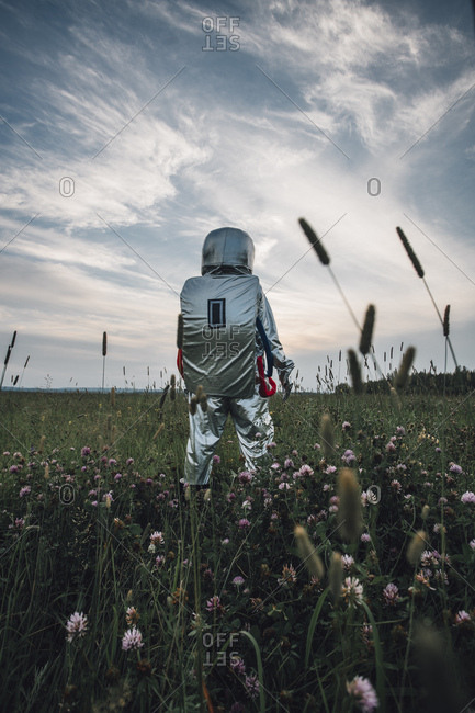 Spaceman exploring nature- standing in meadow- looking at sky