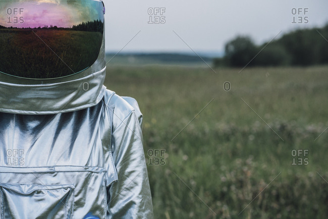 Spaceman exploring nature- meadow reflecting in space hat