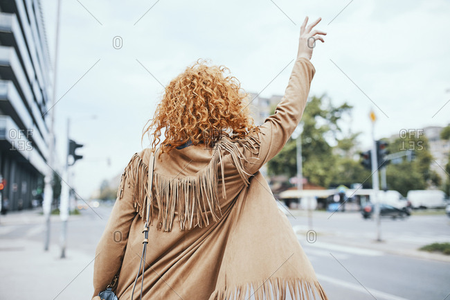 Redheaded woman hailing a taxi in the street
