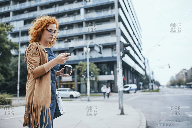 Young woman waiting to cross road- using smartphone