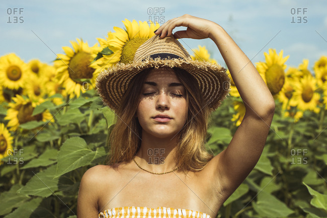 Young woman holding a straw hat on her head in a field of sunflowers