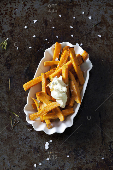 Salted sweet potato fries with rosemary and mayonnaise in porcelain bowl