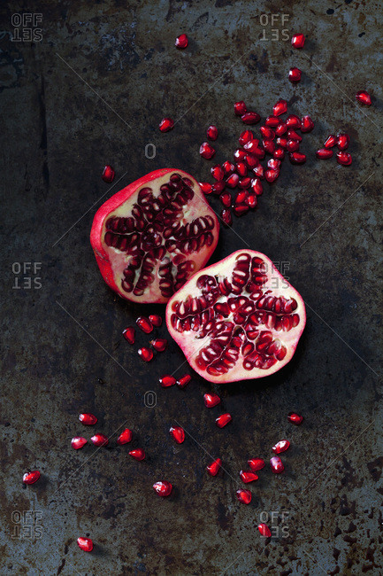 Two halves of pomegranate and pomegranate seed on dark metal