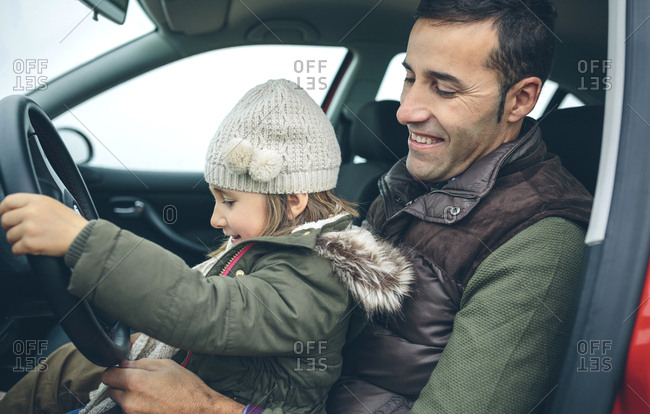 Happy little girl with wool cap driving car sitting on father's lap