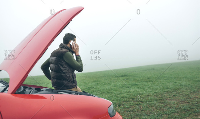 Man talking on cell phone next to broken car