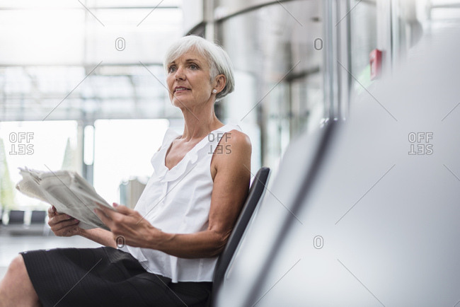 Senior woman sitting in waiting area with newspaper