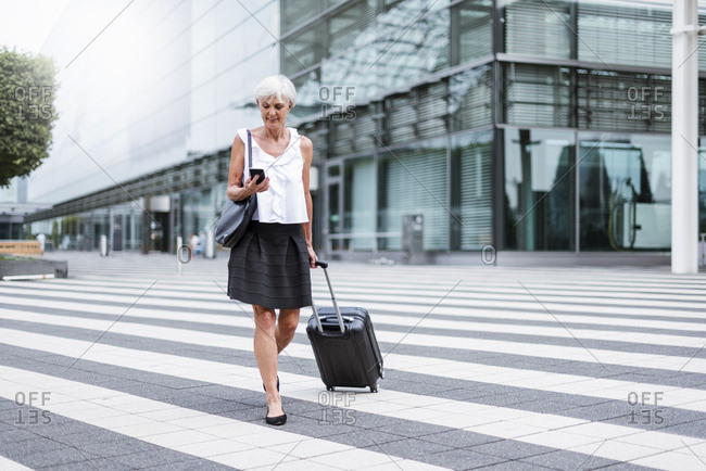 Smiling senior woman with baggage on the move looking on cell phone