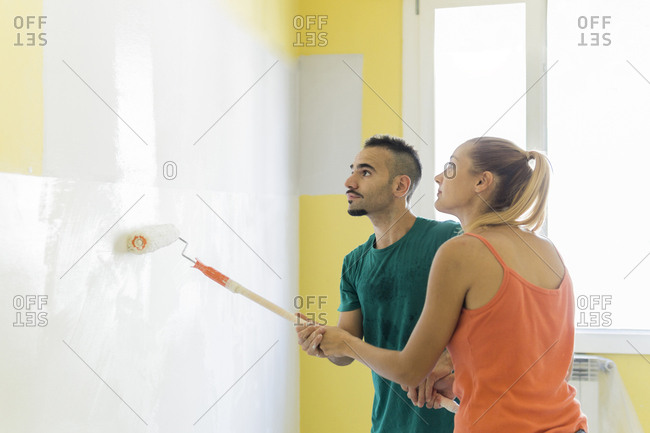 Couple painting wall together at new home