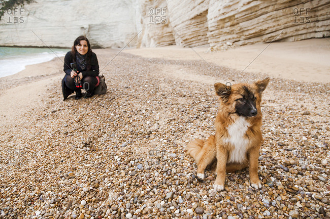 Italy- Vieste- stray dog sitting on Vignanotica Beach while smiling woman crouching in the background