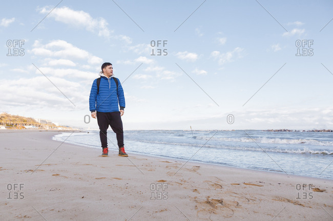 Italy- Molise- Termoli- young man standing at the beach- looking at distance