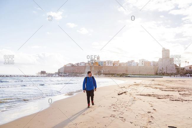 Italy- Molise- Termoli- young man walking at the beach