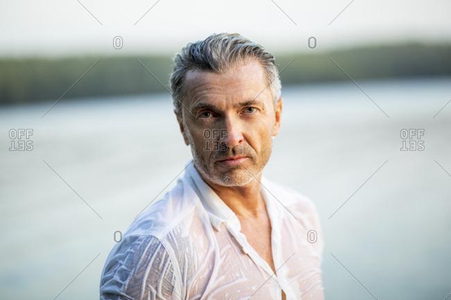 Portrait of mature man wearing wet white shirt at lake
