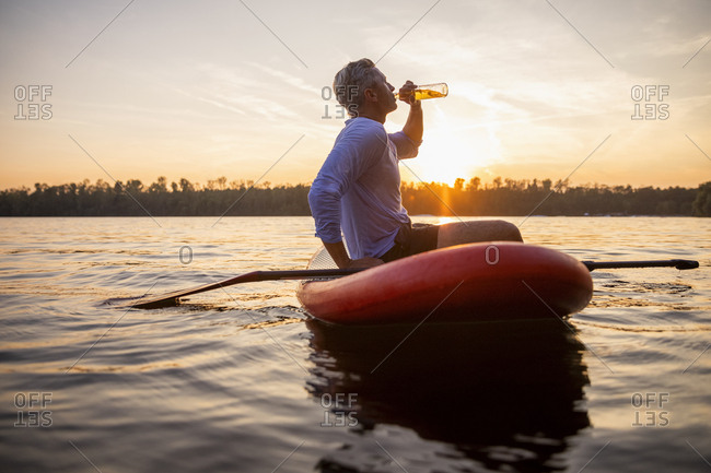 Man sitting on paddleboard on a lake by sunset drinking beverage