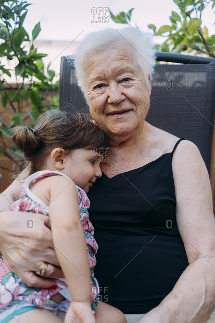 Portrait of smiling Grandmother spending tome with her granddaughter on terrace