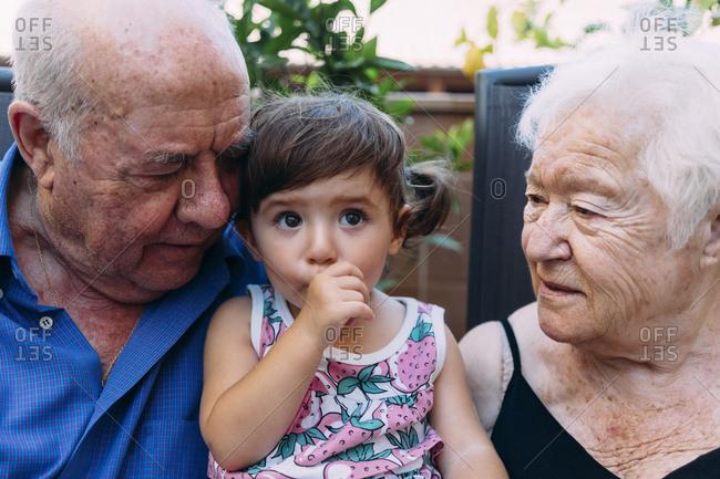 Grandparents looking at baby girl sucking thumb