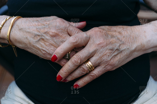 Hands of senior woman with golden rings and red painted nails