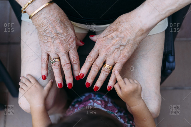 Hand of baby girl pointing on hand of senior woman with rings and red painted nails