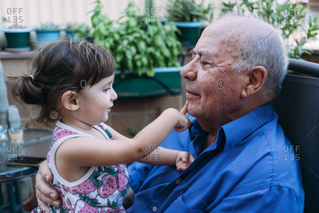 Grandfather and baby girl playing together on the terrace