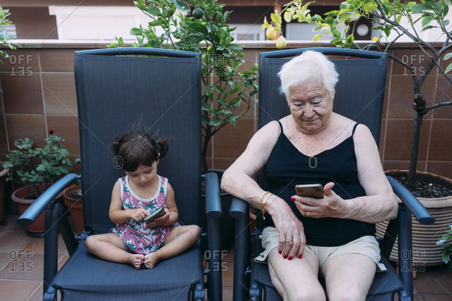 Grandmother and baby girl sitting side by side on the terrace using mobile phones