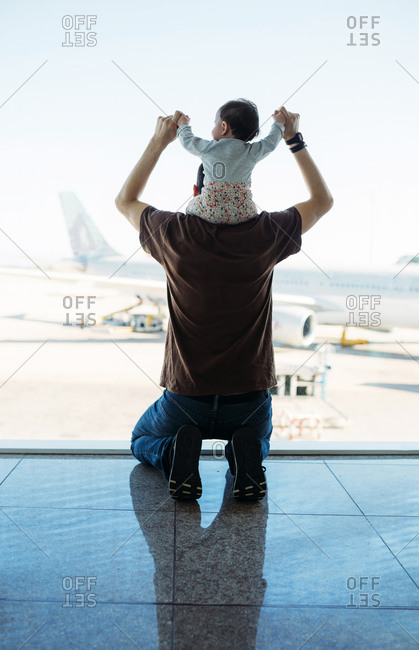 Man carrying a baby girl on his shoulders at the airport and looking at the airplanes- rear view