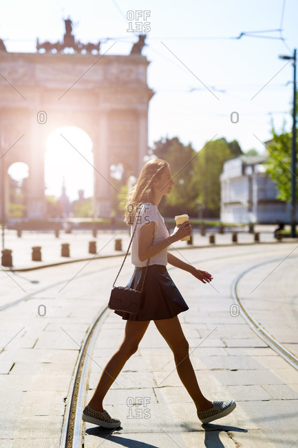 Italy- Milan- young woman walking in the city