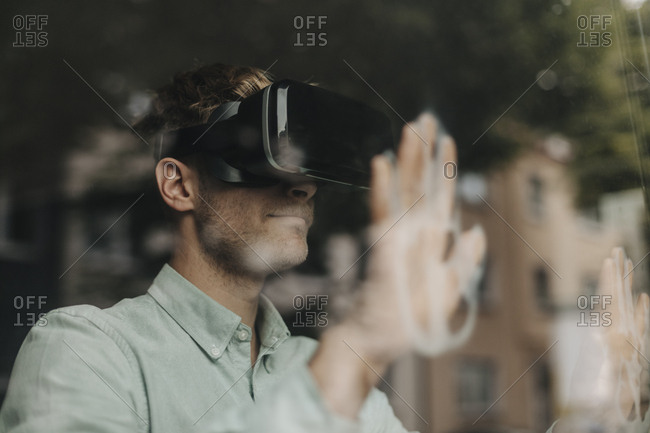 Young man standing at the window- using VR glasses