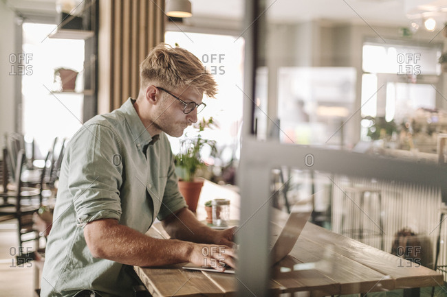 Young man working in his start-up cafe- using laptop