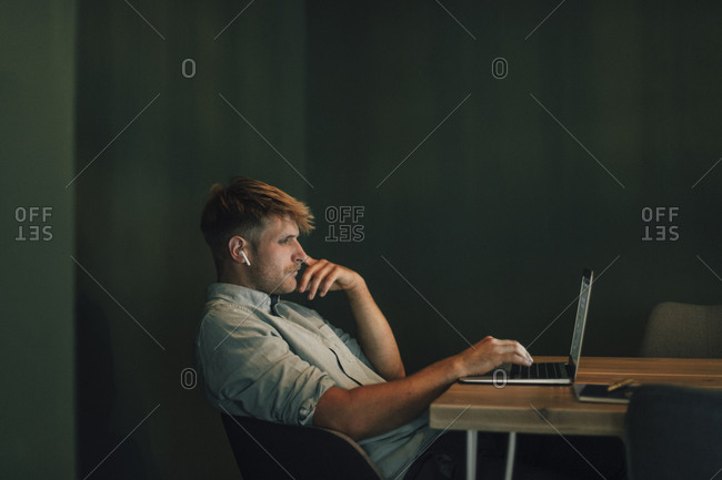 Man sitting in office- working late in his start-up company- listening music