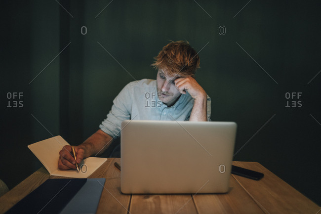 Man sitting in office- working late in his start-up company- taking notes