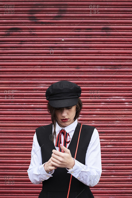 Fashionable woman with red lips wearing black peaked cap standing in front of red roller shutter