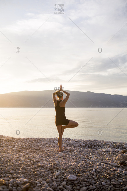 Young woman doing yoga on a stony beach at sunset- tree position