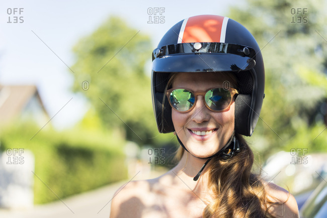 Portrait of smiling woman wearing sunglasses and motorcycle helmet